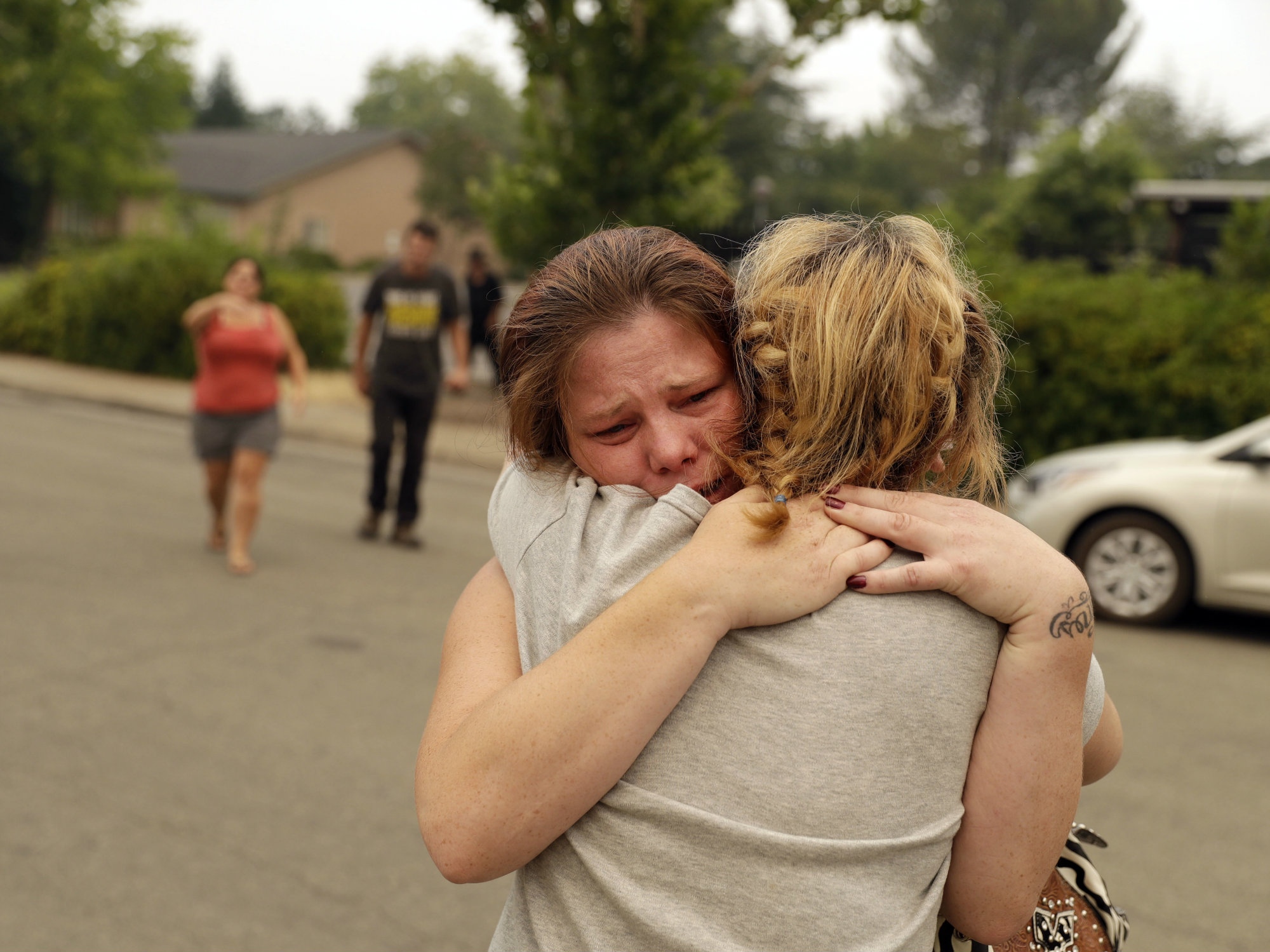 Carla Bledsoe, facing camera, hugs her sister Sherry outside of the sheriff's office after hearing news that Sherry's children, James and Emily, and grandmother, Melody Bledsoe, were killed in a wildfire Saturday, July 28, 2018, in Redding, Calif.